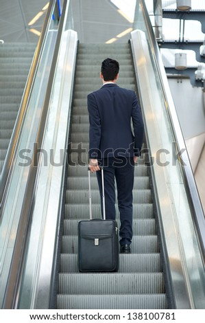 Business man going up escalator holding travel bag - rear view - stock photo