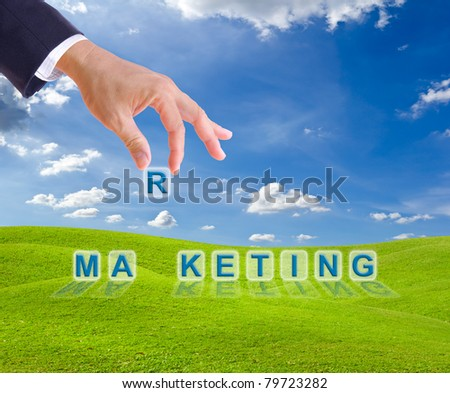 business man hand and marketing word buttons on green grass meadow - stock photo