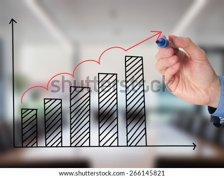 Business man hand drawing a graph. Growth concept. Isolated on office background. Stock Image - stock photo