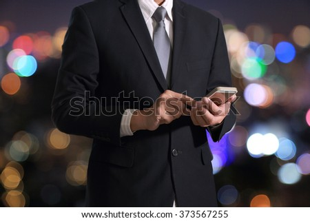 Business man hand hold and touch screen smart phone, mobile on blurred abstract bokeh background as communication Concept. - stock photo