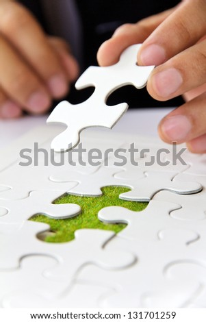 business man hand holding a puzzle piece, green space concept - stock photo