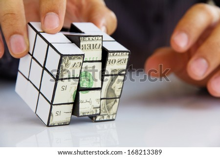 business man hand holding a rubik's cube,money concept - stock photo