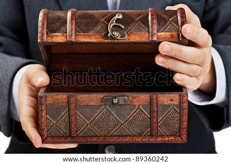 Business man hand holding old antique brown wood treasure chest or box white isolated - stock photo