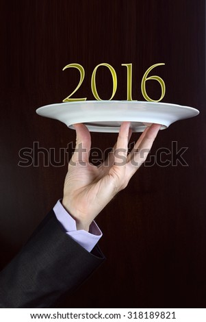 Business man hand holds on a plate 2016. New Year concept. - stock photo