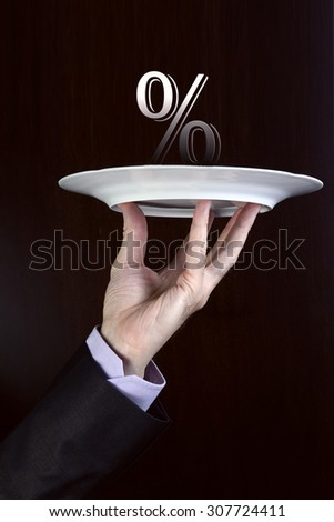 Business man hand holds on a plate percentage sign - stock photo