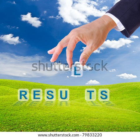 business man hand made results word buttons on green grass meadow - stock photo