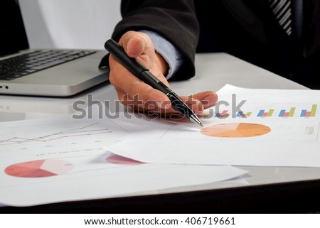 Business man hand pointing at business document during discussion at meeting - stock photo