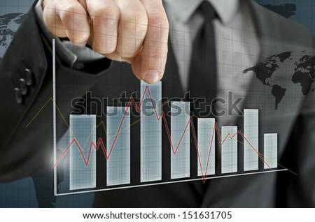 Business man hand pulling upwards column of interactive business graph. - stock photo