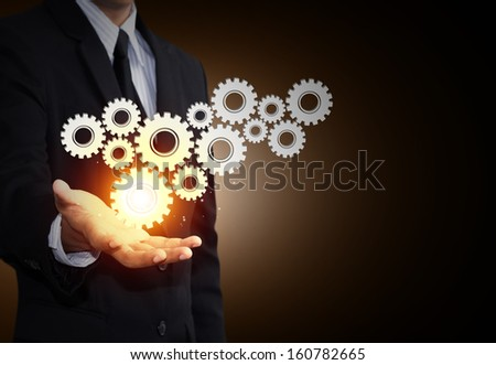Business man hand show gear to teamwork as concept - stock photo