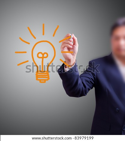business man Hand with pen drawing light bulb - stock photo