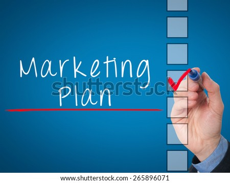 Business man hand  writing marketing plan concept and ticking check list. Isolated on blue background. Stock Image - stock photo