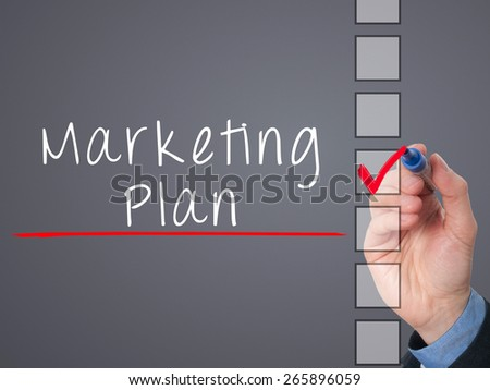 Business man hand  writing marketing plan concept and ticking check list. Isolated on grey background. Stock Image - stock photo