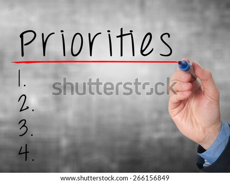 Business man hand writing Priorities list with marker isolated on grey. Stock Image - stock photo