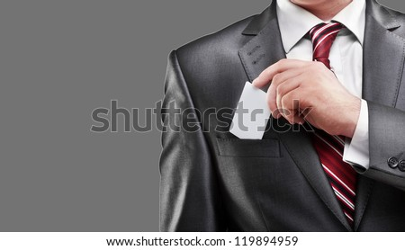 Business man handing a blank business card isolated on gray background High resolution - stock photo