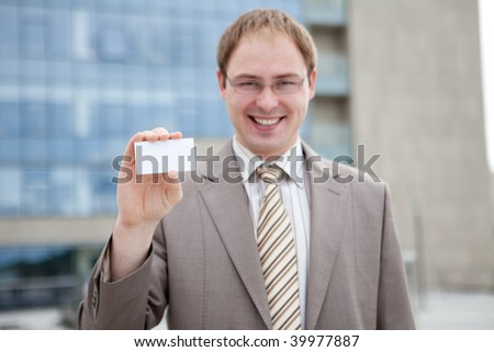Business man handing a blank business card (outdoor the office)