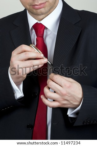Business man handing out a pen to sign a contract - stock photo