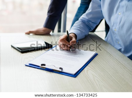 Business man hands signing on document at his desk - stock photo
