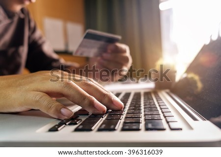 Business man hands using laptop and holding credit card with digital layer effect diagram as Online shopping concept - stock photo
