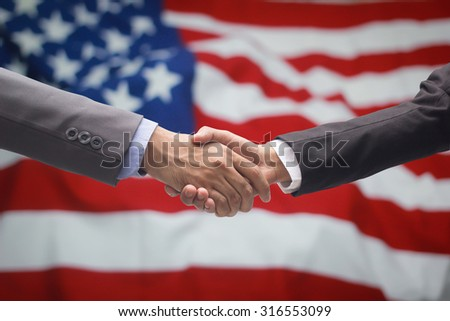 Business man handshake over blur crumpled and creased fabric textures of American flag with vignette backgrounds. business hands concept.international business communication symbolic concept. - stock photo