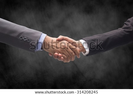 business man handshake over grunge chalkboard backgrounds textures : business handshaking with partner for agreement ,trust and successful together.business hand concept.