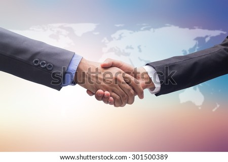 business man handshake over map on blurred beautiful twilight sky backgrounds, business hands concept.pastel tone backgrounds. - stock photo
