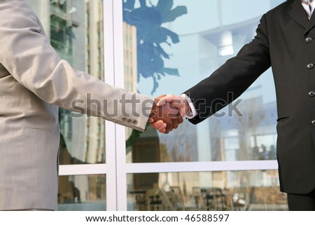 Business man handshake with office building in background - stock photo
