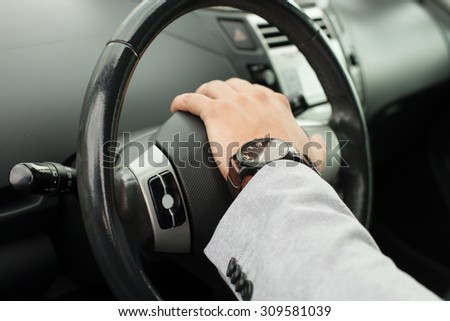 Business man has his hand on the wheel the car