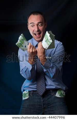 Business man has just earn a lot of money. His pockets are full of money, and his expression is of total success. Conceptual image for becoming rich, business success, and so on. - stock photo