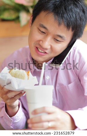 business man having lunch and eat fast food in a restaurant, asian - stock photo