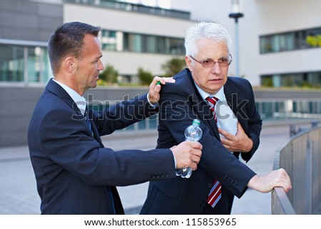 Business man helping senior with heart attack with a bottle of water - stock photo