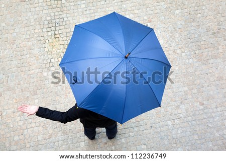 Business man hidden under umbrella and checking if it's raining - stock photo