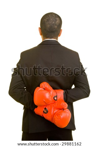 Business man hiding boxing gloves behind his back - stock photo