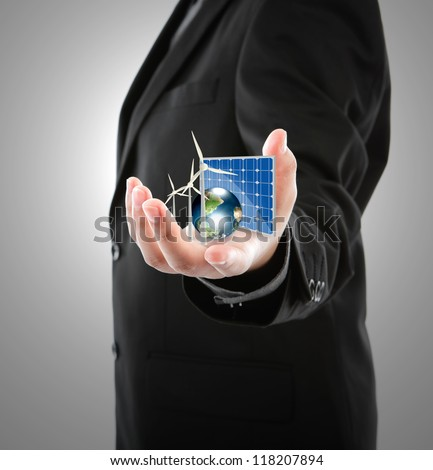 Business man hold Alternative Energy (solar cell, earth, wind turbine ) Elements of this image furnished by NASA