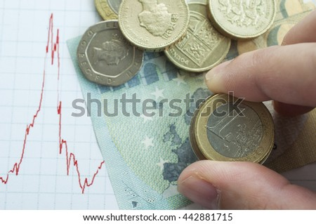 Business man hold Euro coins on Euro banknotes while British decide to leave Euro zone - stock photo