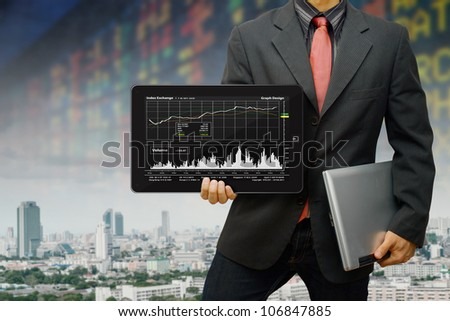 Business man hold the digital tablet and graph report - stock photo