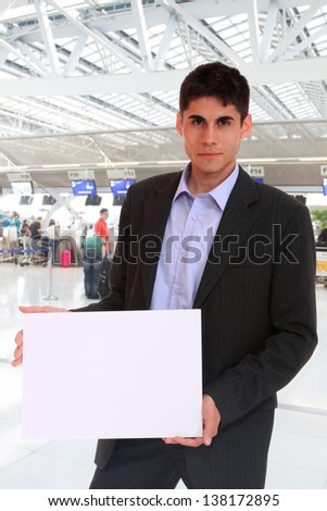 Business man holding a blank board at the airport - stock photo