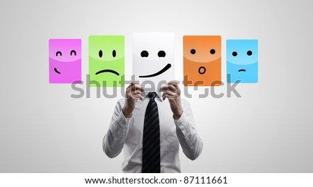 Business man holding a card with smiling face. Man chooses an emotional faces. On a gray background - stock photo