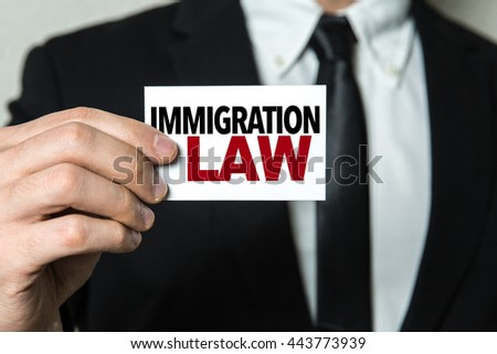 Business man holding a card with the text: Immigration Law - stock photo