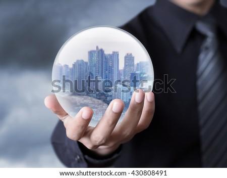 Business man holding a city inside a sphere, City of the future