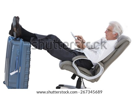 business man holding a digital tablet  while sitting in the airport in business lounge  sitting with foot on his luggage - stock photo