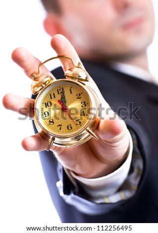 Business man holding a golden clock in hand - stock photo