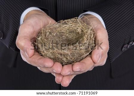 Business man holding a little empty nest - stock photo
