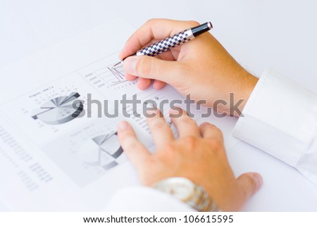 Business man holding a pen in hand analyzing graph and making notes