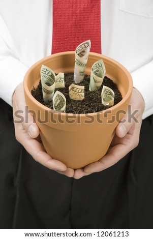Business man holding a pot with multipule denominations of paper bills planted - stock photo