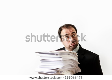 business man holding a stack of paper not looking to pleased