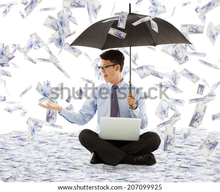 business man holding a umbrella and catching money - stock photo