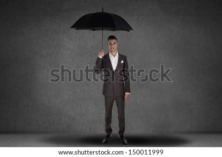 Business man holding an umbrella - stock photo