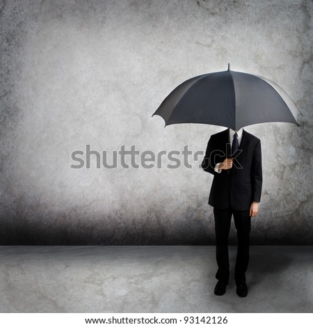 Business man holding an umbrella - stock photo