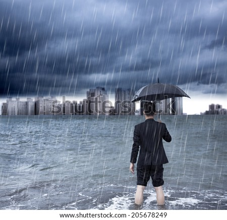 business man holding an umbrella and standing  with cloudburst background - stock photo
