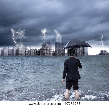 business man holding an umbrella with thundershower background - stock photo